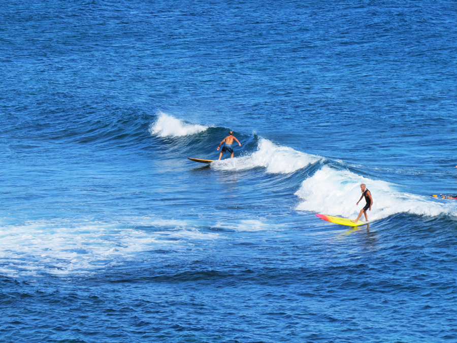 Surfers riding waves along the Road to Hana