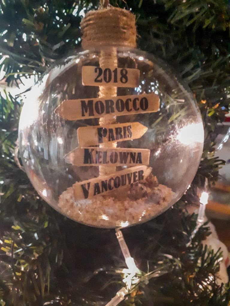Glass bauble with road sign featuring countries and cities