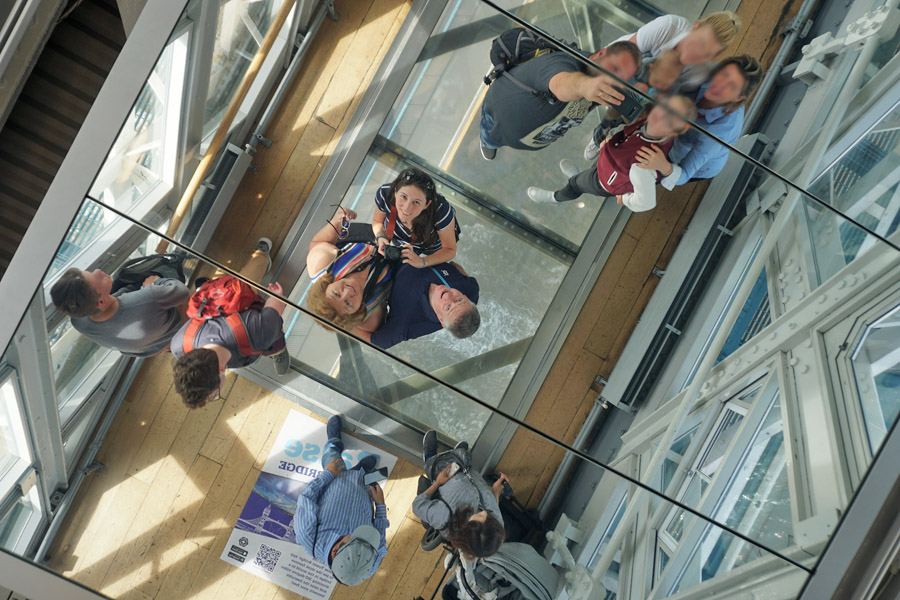 Tourists on the glass walkway atop the Tower Bridge in London