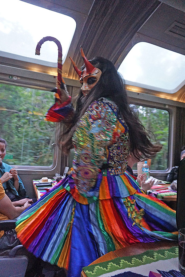 Dancer in a colorful folk costume on the train to Cusco