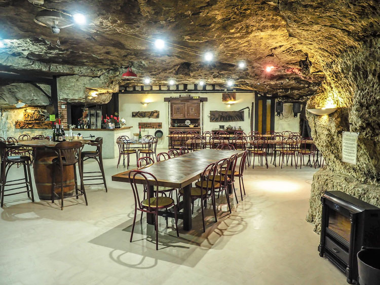 Tables and chairs in a restaurant inside a troglodyte cave in France
