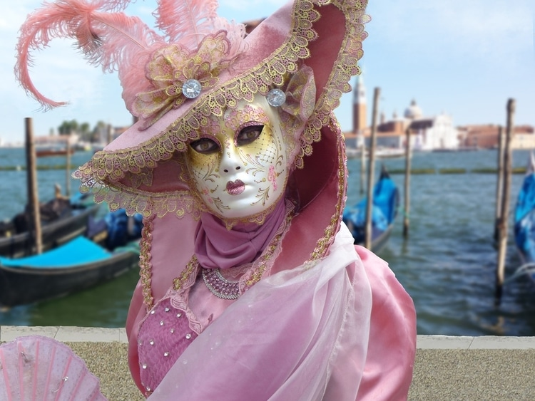 Woman in a mask and pink dress at Carnival in Venice