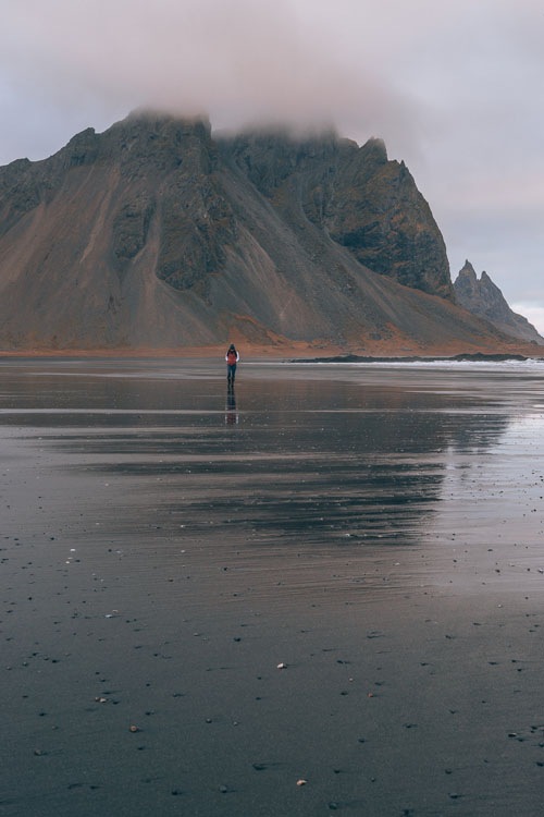 Woman on the beach in the Vestrahorn Mountains in Iceland