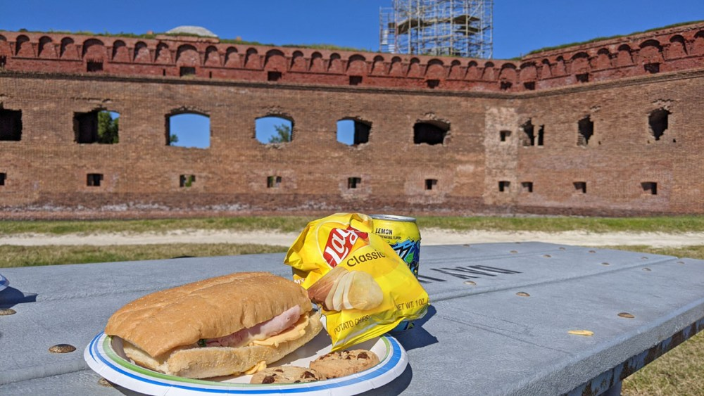 Lunch of a sandwich, chips, and cookies on a picnic table in front of Fort Jefferson