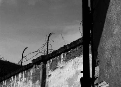 A desolate wall topped with broken barbed wire marks the edge of the Terezín Concentration Camp/Prison.