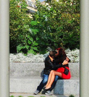 Parisian lovers kissing on a concrete wall.
