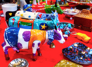Brightly multi-colored ceramic cows stand beside other goods.