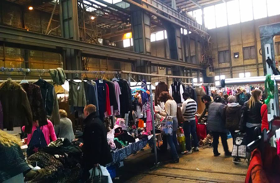 Racks of used clothing are lined up in the cavernous building of IJ-Hallen