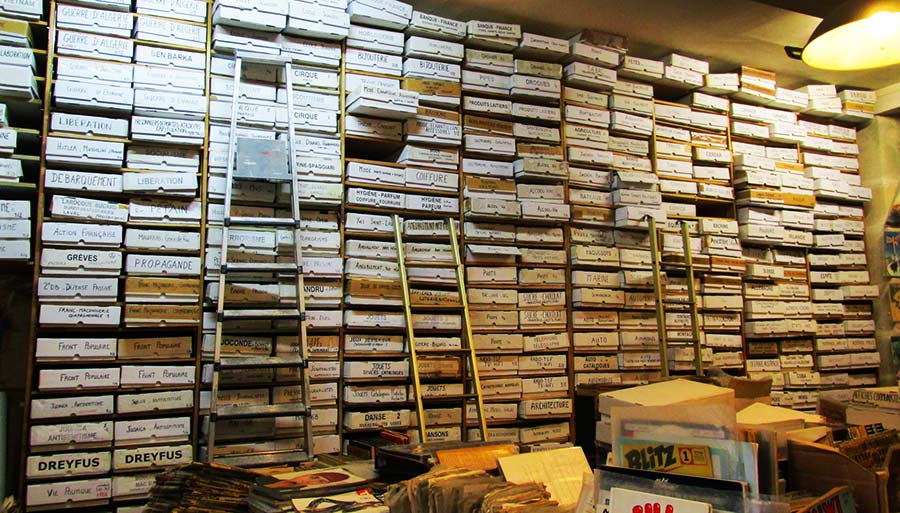 Walls are lined with shelves stacked with boxes of flt files, and ladders to reach them all.