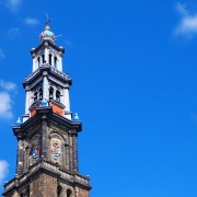 The tower of the Amsterdam Westerkerk against a bright blue sky