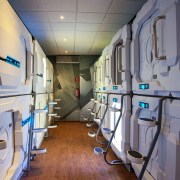 A look into the capsule/pod area at Izzzleep Capsule Hotel, showing the two levels of pods anda the steps to ge to the upper-level pods.