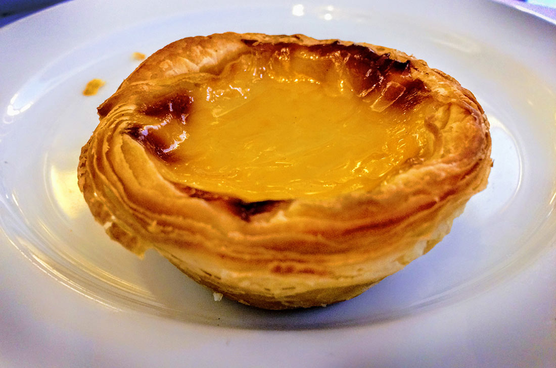 A pastel de nata, or Portuguese custard tart, with its flaky, layered crust and egg custard filling.