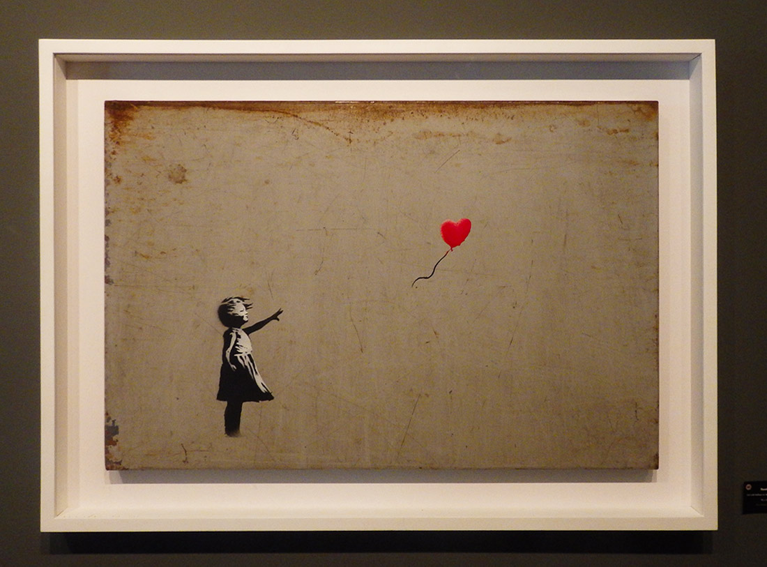 "One of many instances of Banky's ""Girl with Balloon,"" showing a young girl who has just let go of (or lost) a red, heart-shaped balloon."