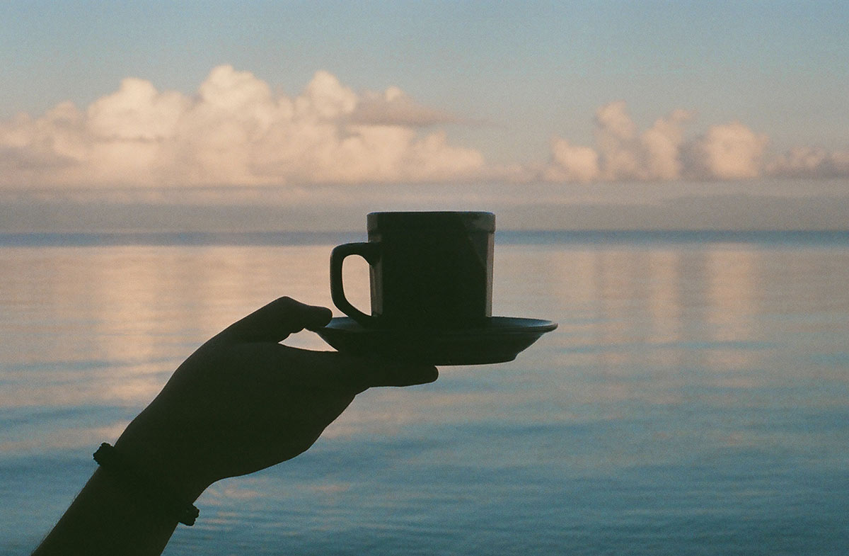 Silhouette of a hand holding a cup and saucer with the open sea in the background.