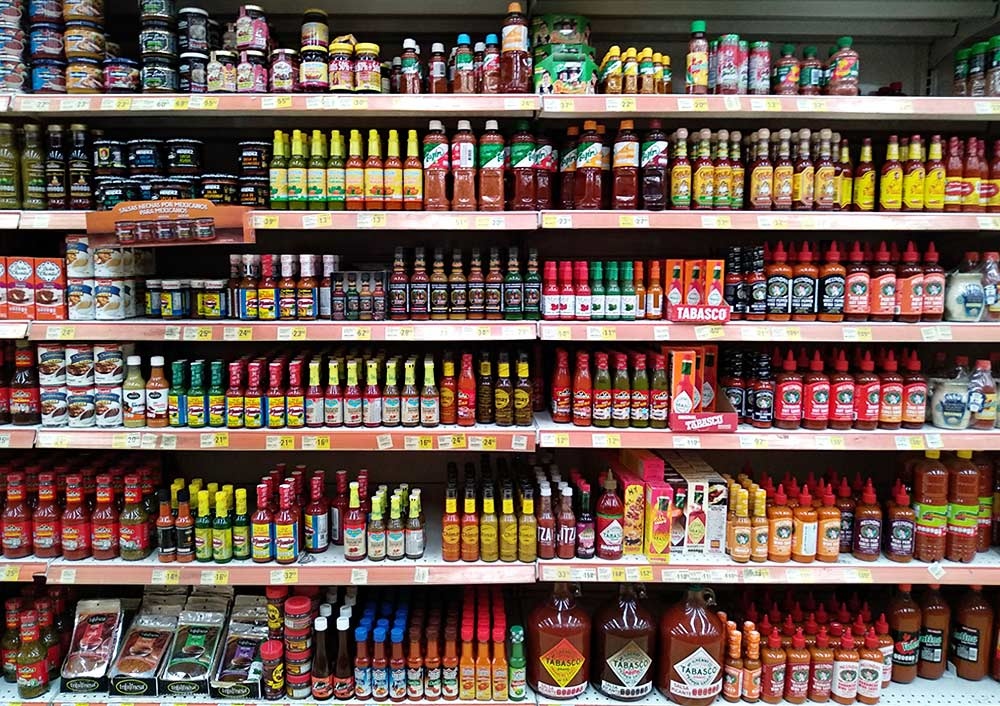 A Mexican supermarket section six shelves high and many feet wide full of hot sauces and salsas. And this is only part of it! Dozens of types and brands.
