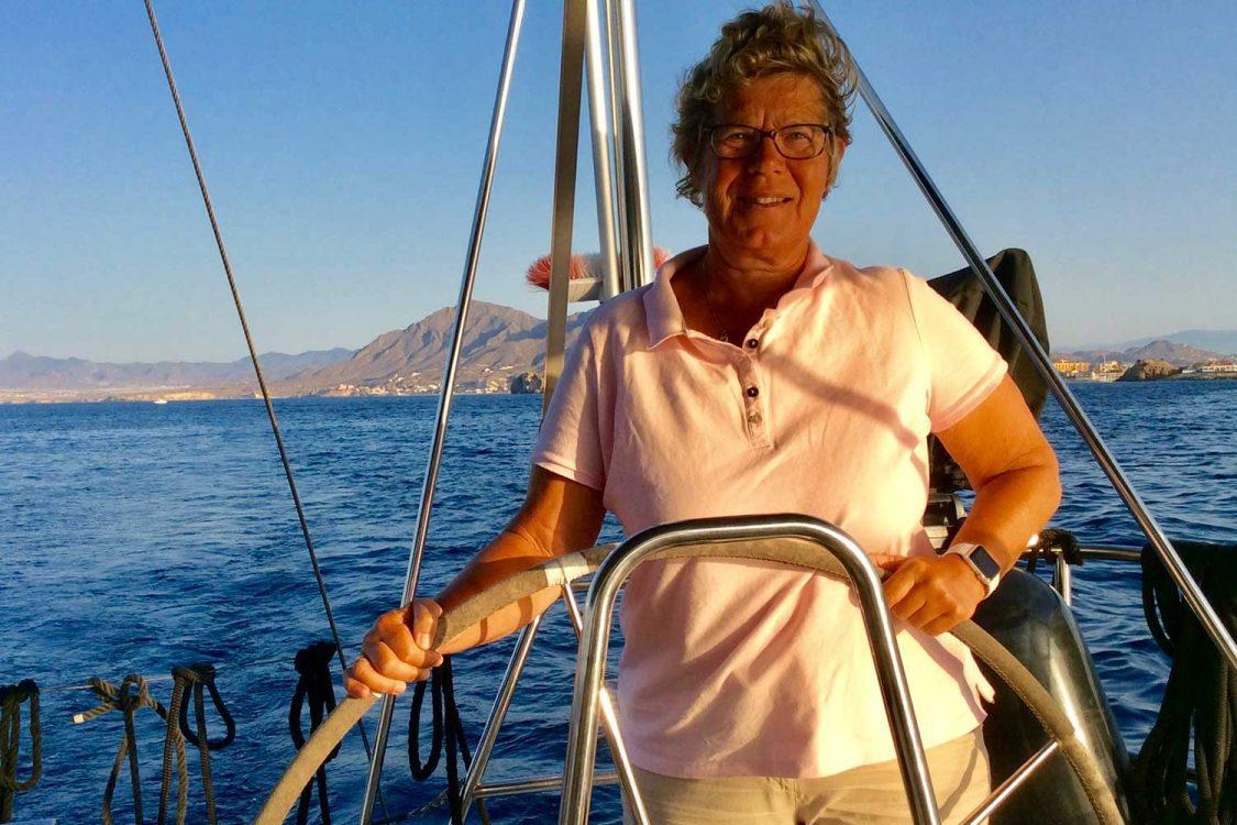 Zeilend langs de Spaanse kust heeft Ankie het roer van de Nomas stevig in handen.