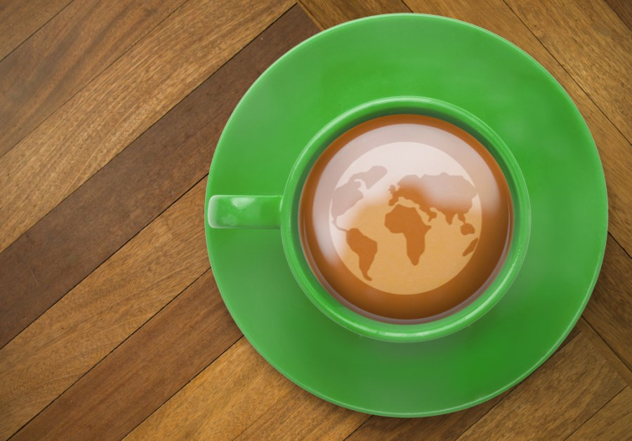 Earth against wooden surface with planks in a cup of tea