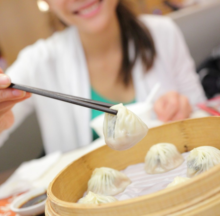 Xiao long bao / xiaolongbao soup dumplings. Woman eating Chinese Shanghainese steamed dumpling buns with chopsticks in restaurant in China.