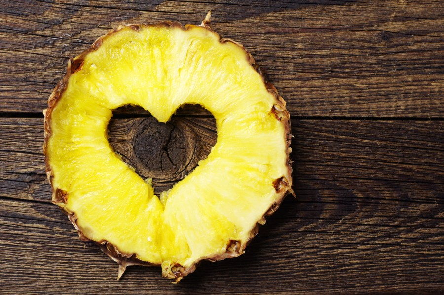 Sliced pineapple with a cut in shape of hearts on vintage wooden background