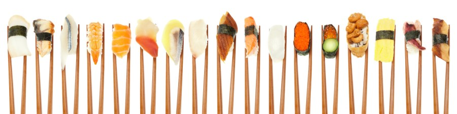 A pair of chopsticks grips but doesn't crush food - 17 different types of sushi being held up in a row with wooden chopsticks isolated on white.