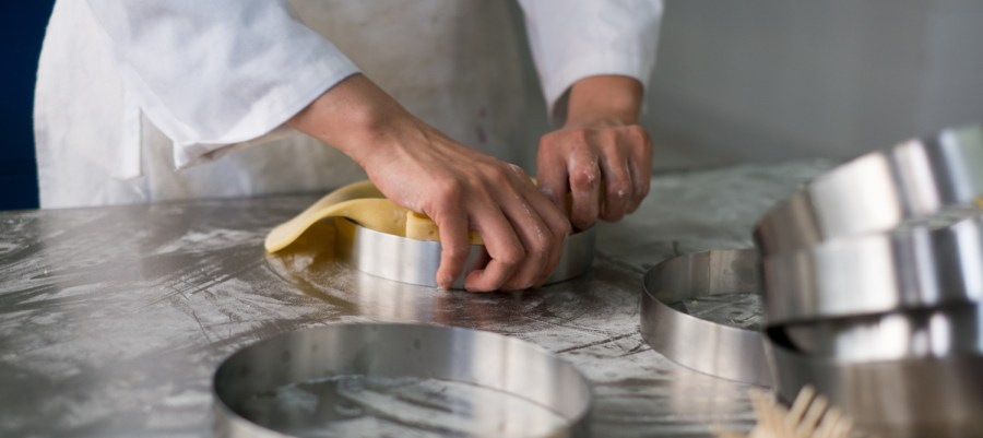 a stainless steel top is an even better conductor of heat - Pastry chef's hands pulling pit dough into a stainless steel pie crust ring sitting on flour dust covered stainless steel prep table.