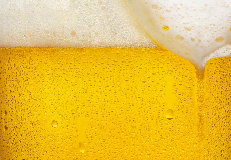 Creamy foam on beer and carbon dioxide bubbles