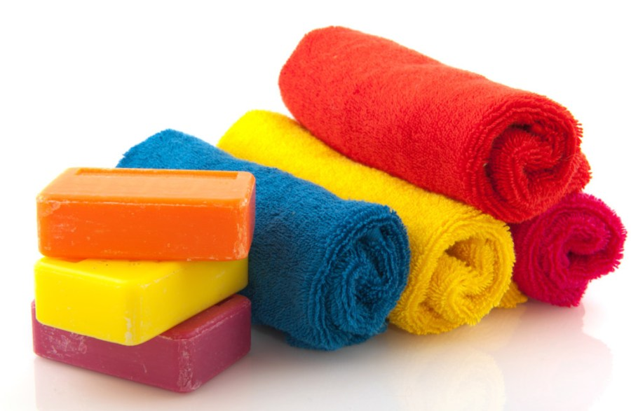 soap is an emulsifier that creates an emulsion of water and grease, making it easy for the former to wash off dirt - colorful rolled towels with bars soap isolated over white