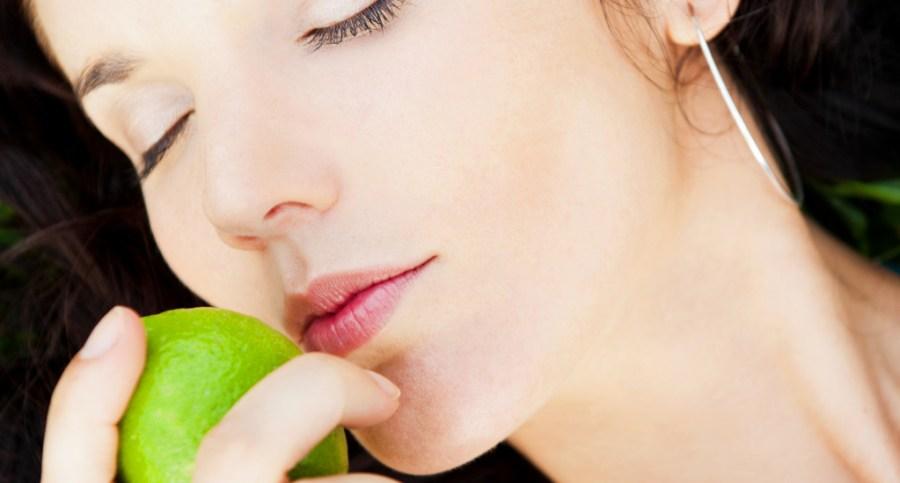 Pretty brunette girl wearing elegant dress relaxing outdoor in green grass and smells aromatic lemon or lime citrus