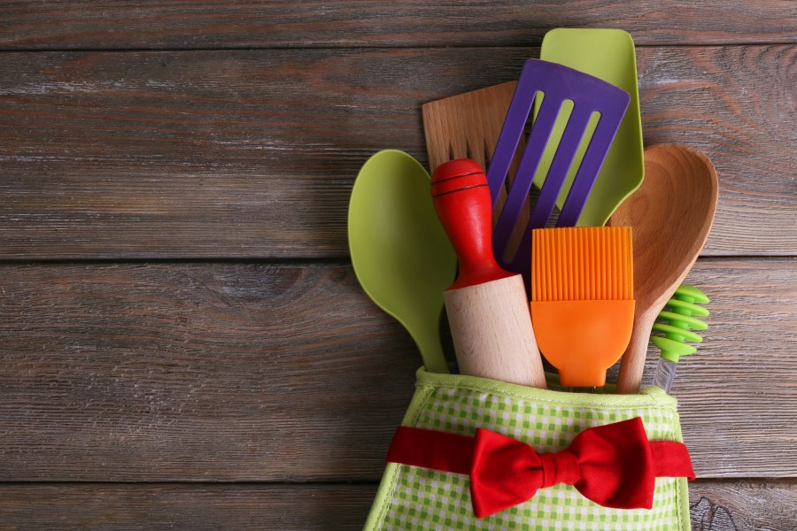 Silicone spatula in a Set of kitchen utensils in mitten on wooden planks background