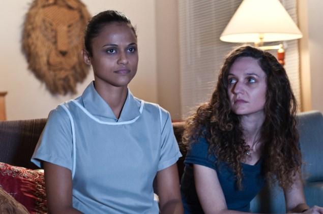 A patroa Helena (Helena Albergaria) e a empregada Paula (Naloana Lima) assistem tv juntas (Crédito da foto: Gabriel Chiarasteli)