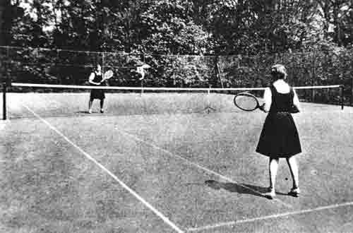 Pupils playing tennis, the courts are now overgrown