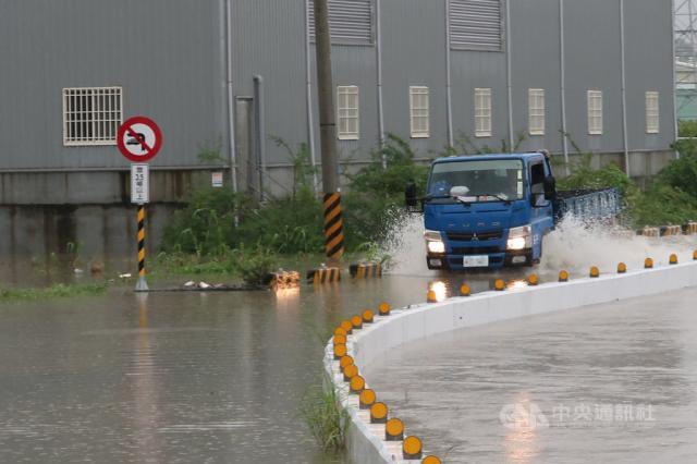 高雄市岡山區五甲尾排水溝26日因豪雨不斷已近滿水位,河水溢流到便道,造成附近人車通行困難。中央社記者王淑芬攝 109年8月26日