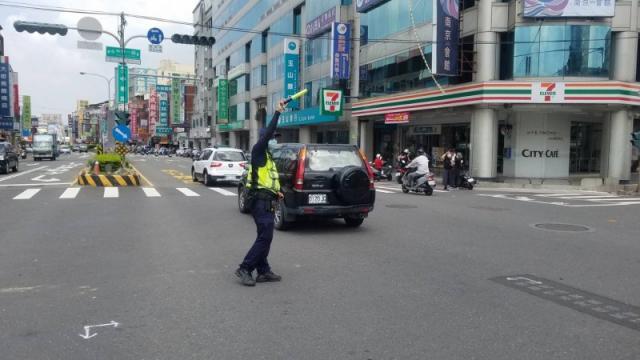 台南永康今午因台電地下電纜轉接頭設備突然故障,造成中華路3處交通號誌受到影響,警方趕緊派員指揮交通,彷彿成了「人體紅綠燈」。(記者萬于甄翻攝)