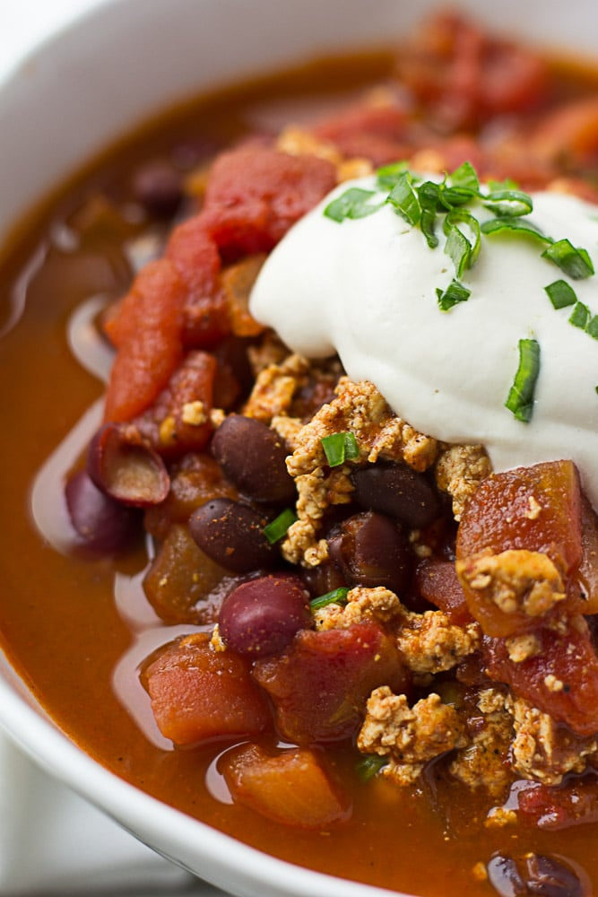 close up shot of vegan chili with sour cream and chives