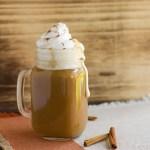pumpkin spice latte in a glass mug with whip cream