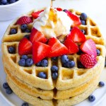 vegan waffles stacked with berries, whip and syrup.