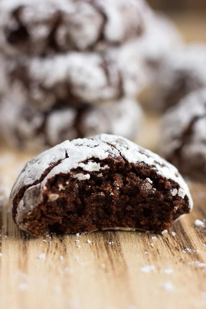 vegan chocolate crinkle cookies, 1 with a bite taken out up close shot.