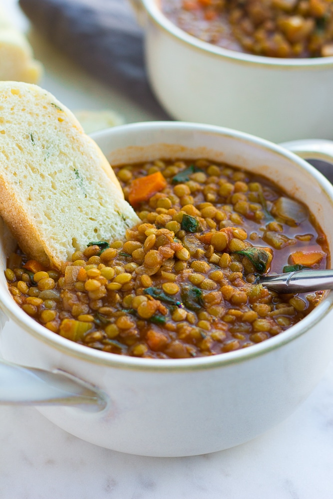close up of vegan lentil soup in a bowl with bread