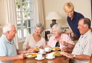Group Of Senior Couples Enjoying Meal Together With Home Help