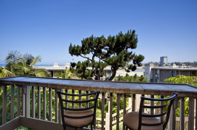 North Coast Village E-101 Balcony View with 2 chairs overlooking a tree, pacific ocean and oceanside harbor