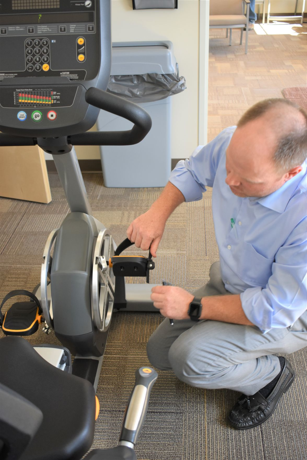 Toby Anderton, orthopedic surgeon, adjusts the pedals on the Matrix ROM-3 bike on Sept. 6 at North Canyon Orthopedics in Twin Falls. JULIE A. FERRARO, TIMES-NEWS