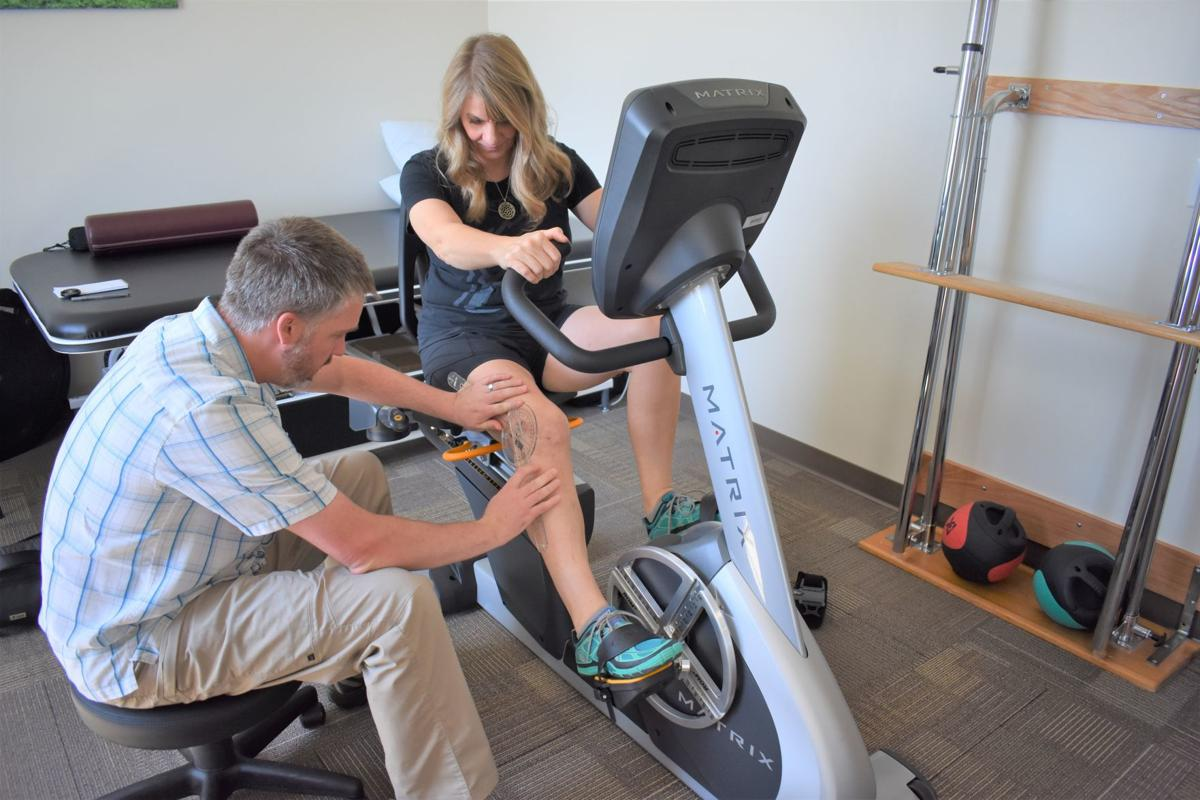 Jeremiah Yates, doctor of physical therapy, measures Shellie Amundson's range of motion Sept. 6 on the Matrix ROM-3 bike Sept. 6 at North Canyon Orthopedics in Twin Falls. JULIE A. FERRARO, TIMES-NEWS