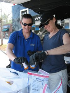 Susan Powell and Colleen Hughes dump pills into evidence bags at the Pittsboro medication drop-off site yesterday