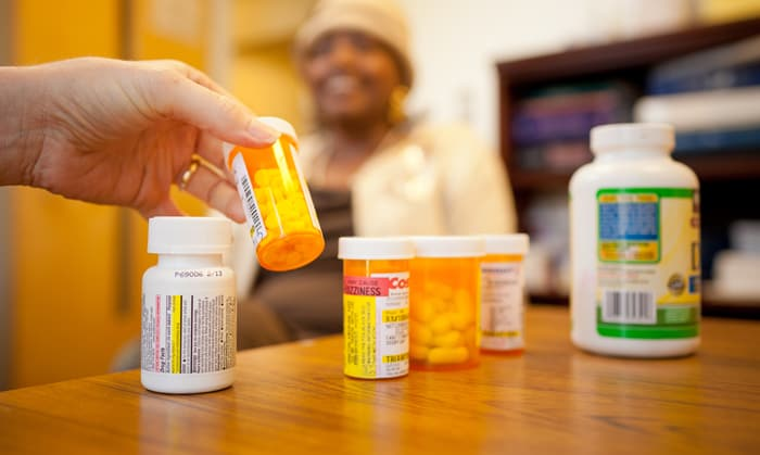 Senior PharmAssist counselor Marilyn Disco checks a client's medications. Photo credit: Jim Colman, Senior PharmAssist
