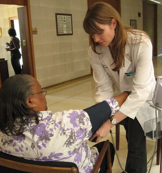 Dr. Sarah Mayer from Wake Forest Baptist Medical Center takes Tracey Johnson's blood pressure at the General Assembly building. Johnson, from Washington County, was in Raleigh to lobby for the day. Photo: Rose Hoban