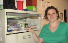 Jenny Gadd displays the medication cabinet in the staff office at the group home. Between them, the three residents have dozens of medications that they take for mental illness and other conditions.