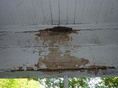 A porch ceiling with peeling lead paint in Greensboro.