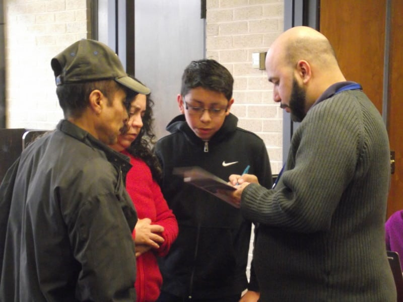 Ricardo Correa of Lincoln Community Health Center assists the Ramos family in registering for the event