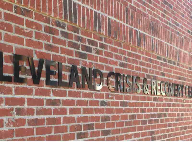 """Photo shows a brick wall with the words """"Cleveland Crisis & recovery Center"""" on it."""