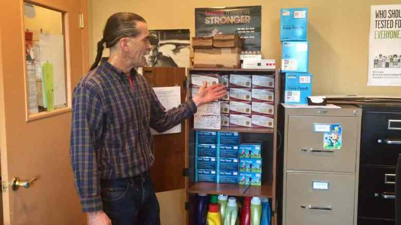Man stands in front of a cabinet full of boxes of syringes